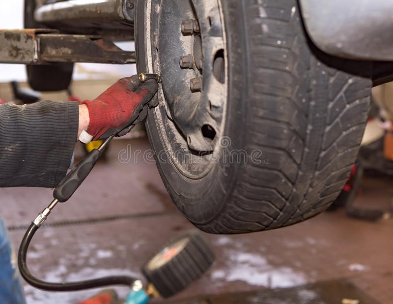 Presión de aire de medición sobre los neumáticos de coche después de cambiar los neumáticos fotos de archivo libres de regalías
