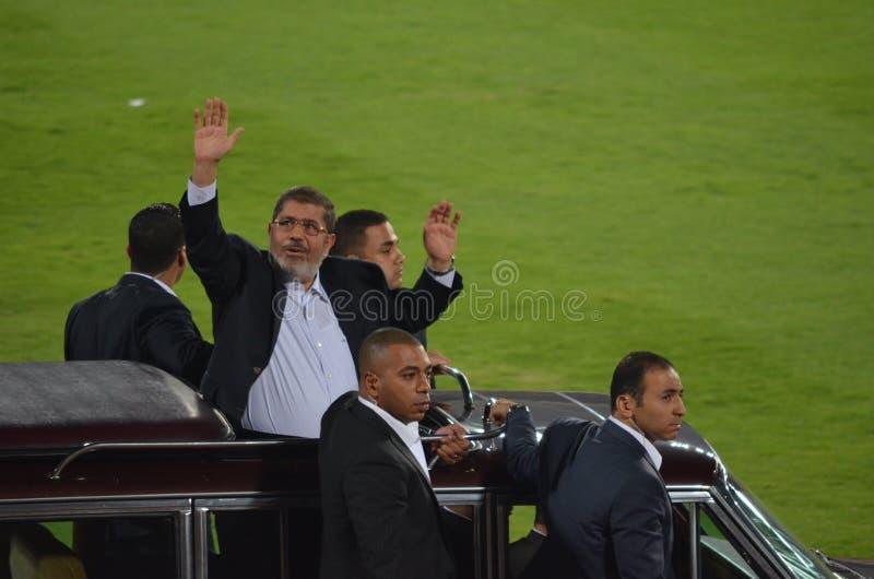 President Mohamed die Morsi aan de mensen golft stock foto