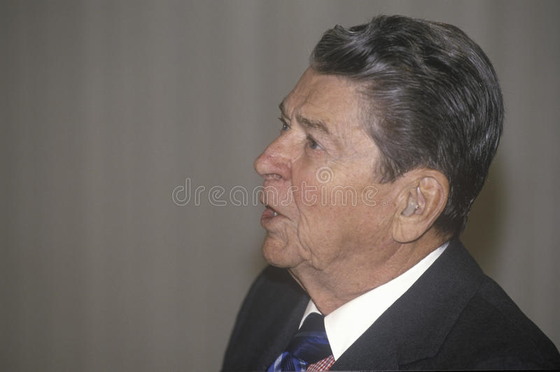 President Ronald Reagan. President Reagan, wearing hearing aid, presents an introduction for the Horatio Alger Association stock photo