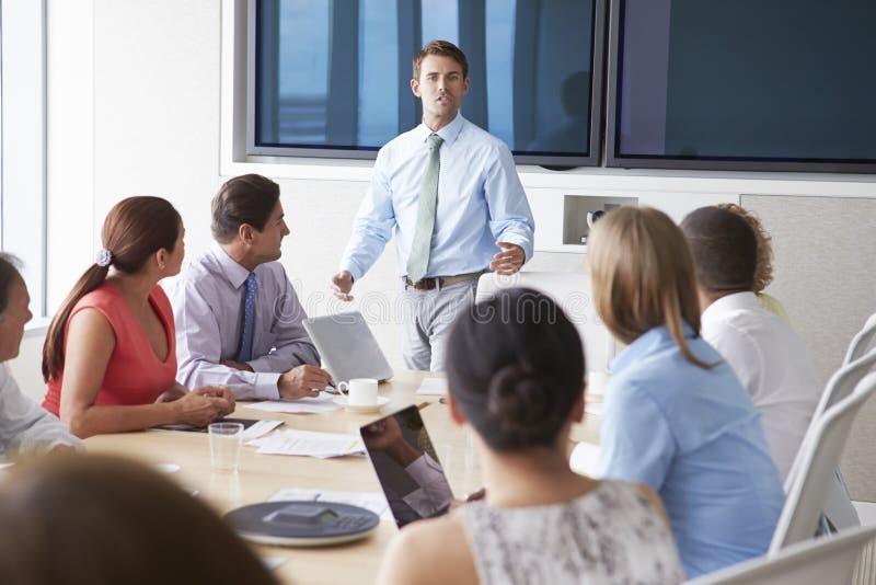 Presidente de motivación que habla con los empresarios en la sala de reunión imagenes de archivo