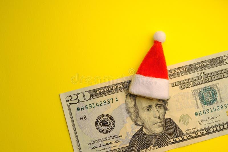 Presidente Jackson que veste um chapéu vermelho de Santa Claus em uma conta de vinte E.U. do dólar em um fundo amarelo brilhante  imagens de stock