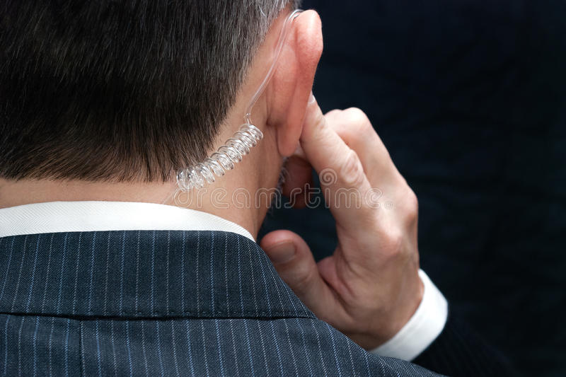 Presidentens säkerhetstjänstmedel Listens To Earpiece, bakom arkivbild