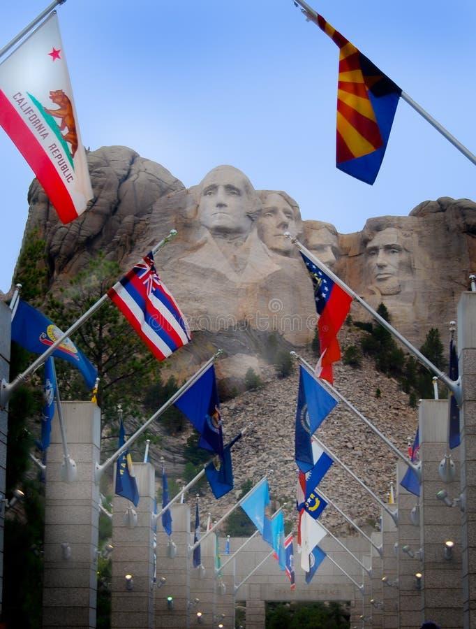 Presidentes Face Carvings del monte Rushmore con vertical de las banderas del estado foto de archivo libre de regalías
