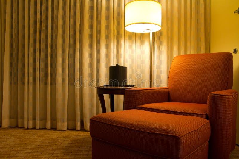Presidenza di rilassamento in un angolo di camera di albergo fotografia stock libera da diritti