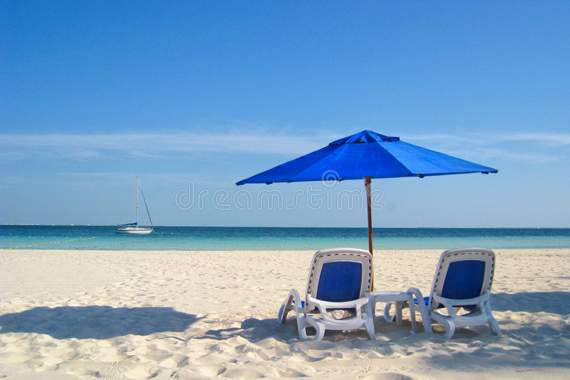 Presidenze ed ombrello di spiaggia dal mare fotografia stock