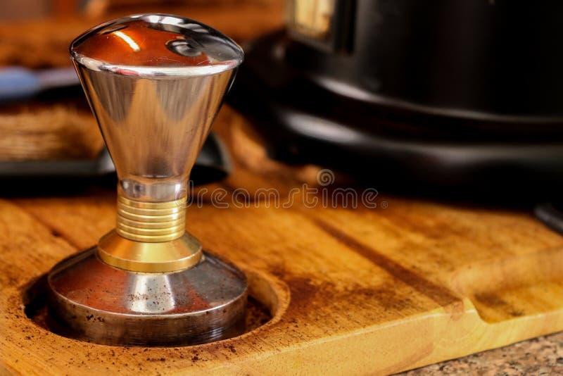 Presionar el café molido con el pisón fotos de archivo