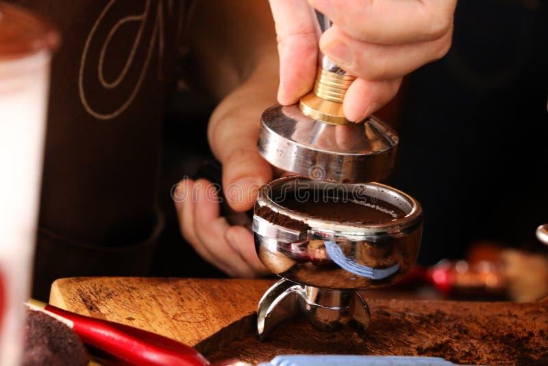 Presionar el café molido con el pisón fotografía de archivo