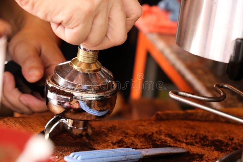 Presionar el café molido con el pisón imágenes de archivo libres de regalías