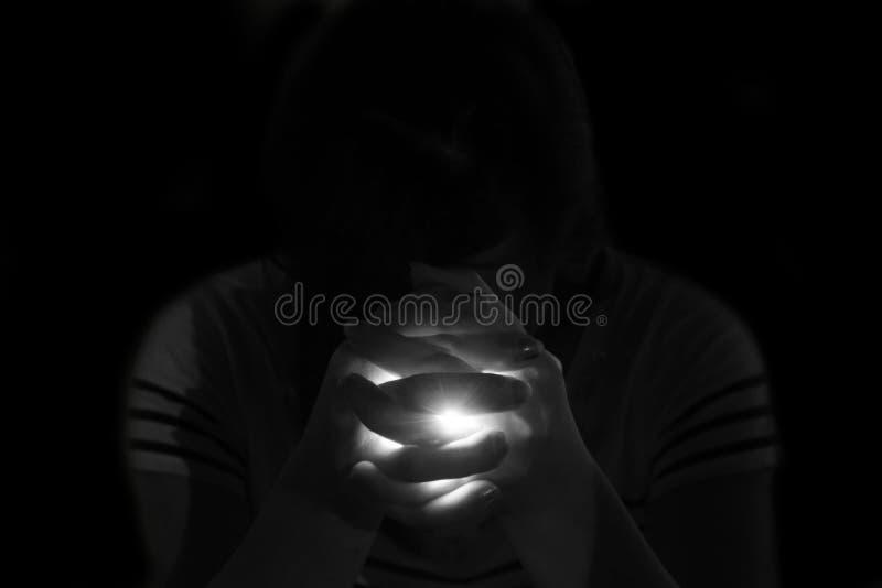 presione a la mujer que ruega en la oscuridad imagen de archivo