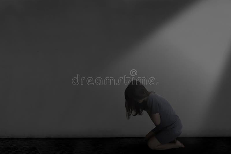 Presione a la mujer que se sienta en la oscuridad foto de archivo libre de regalías