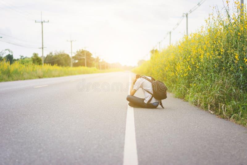 Presione y desesperado, hombre del autostopista del viaje con la mochila fotos de archivo