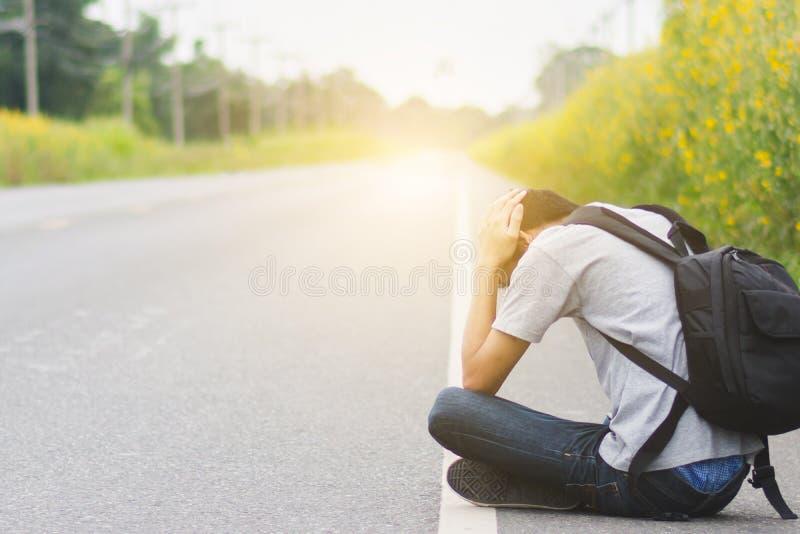 Presione y desesperado, hombre del autostopista del viaje con sitti de la mochila imagenes de archivo