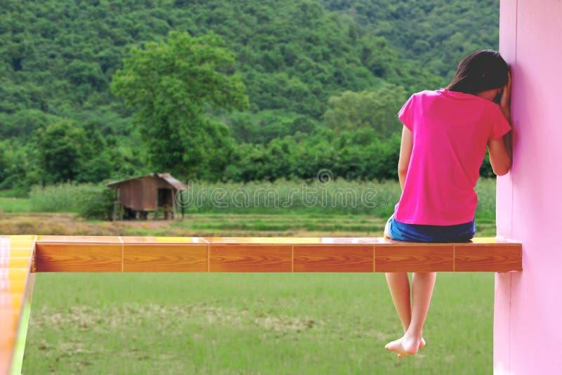 Presione y el sentarse desesperado de la muchacha al aire libre foto de archivo