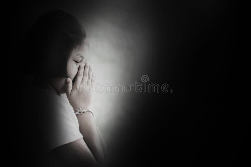 Presione y muchacha desesperada que ruega en la oscuridad foto de archivo libre de regalías