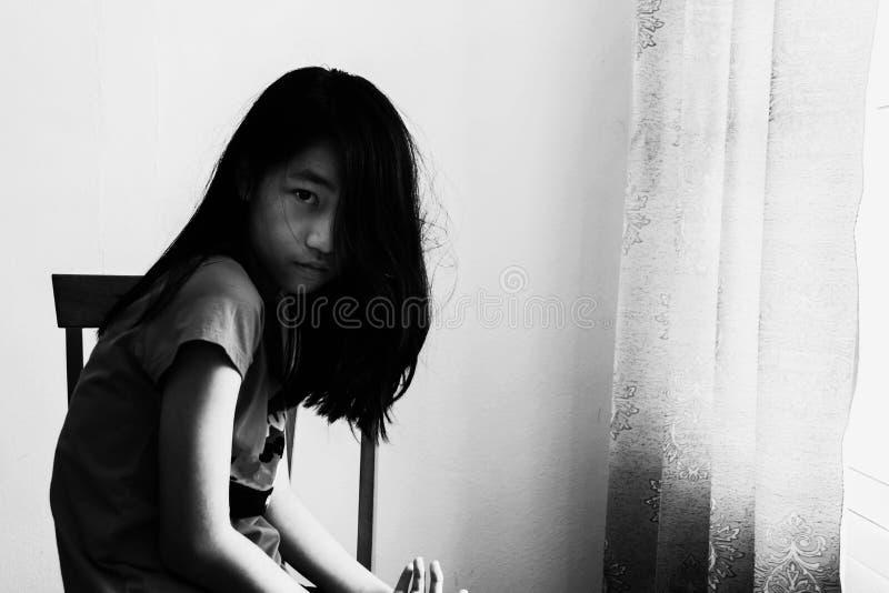 Presione y muchacha desesperada que se sienta en silla en negro fotos de archivo