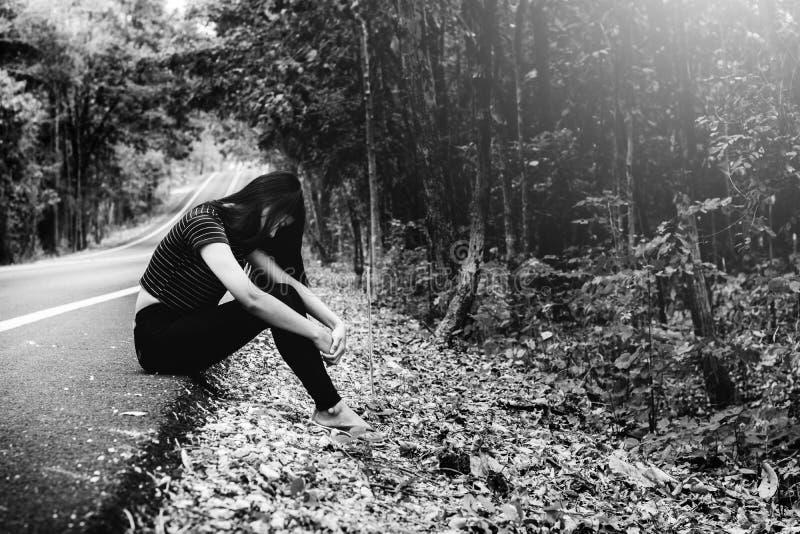 Presione y mujer desesperada, asiática que se sienta en el borde de la carretera foto de archivo libre de regalías