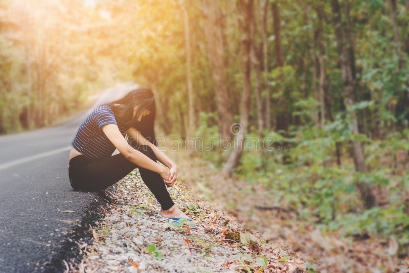 Presione y mujer desesperada, asiática que se sienta en el borde de la carretera foto de archivo