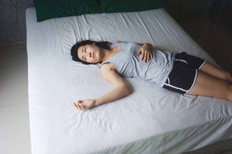 Presione y mujer desesperada que pone en cama imagenes de archivo