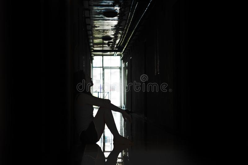 Presione y mujer desesperada que se sienta en la oscuridad fotografía de archivo