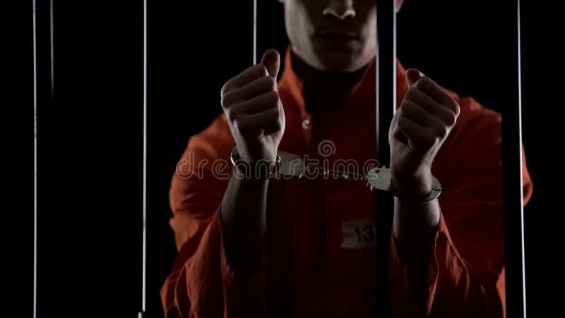 Preso en el uniforme anaranjado que muestra las esposas, pareciendo enojado y decepcionado imágenes de archivo libres de regalías
