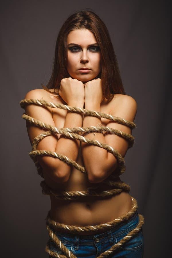 Preso encuadernado de la cuerda de la mujer en fondo del gris de los vaqueros imagen de archivo