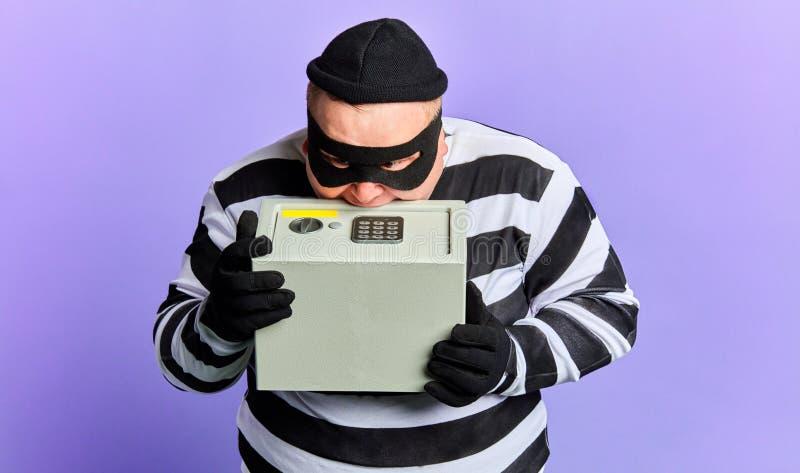 Preso regordete gordo en la ropa rayada que abre la caja fuerte con los dientes imagen de archivo