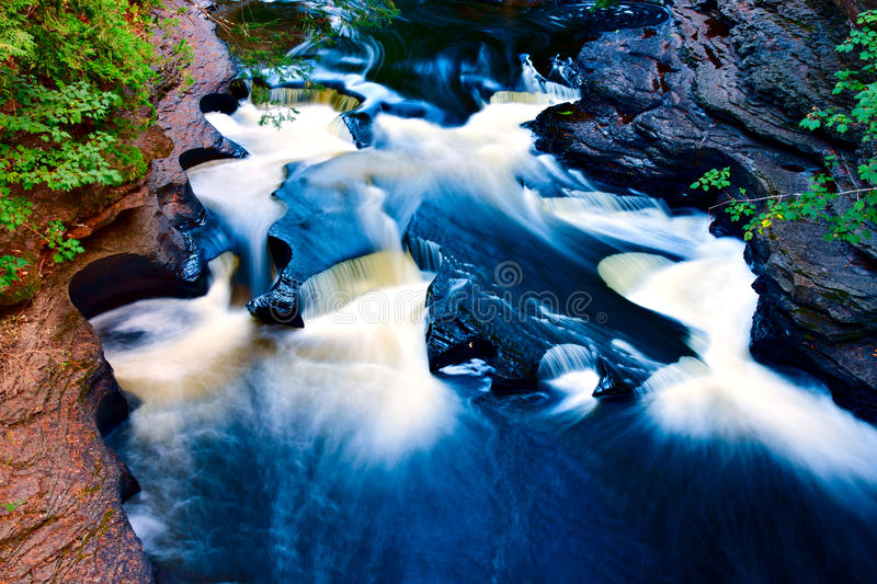 Presque Isle River gorge. The Presque Isle River gorge waterfalls at Porcupine Mountains Wilderness State Park created potholes in the rock formation stock images