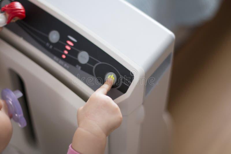 A pressão de mão do bebê o botão do poder no purificador do ar para limpar o ar poluído foto de stock