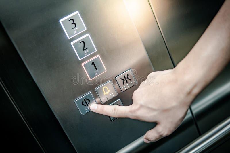 Pressão de mão masculina no botão do estar aberto no elevador fotos de stock