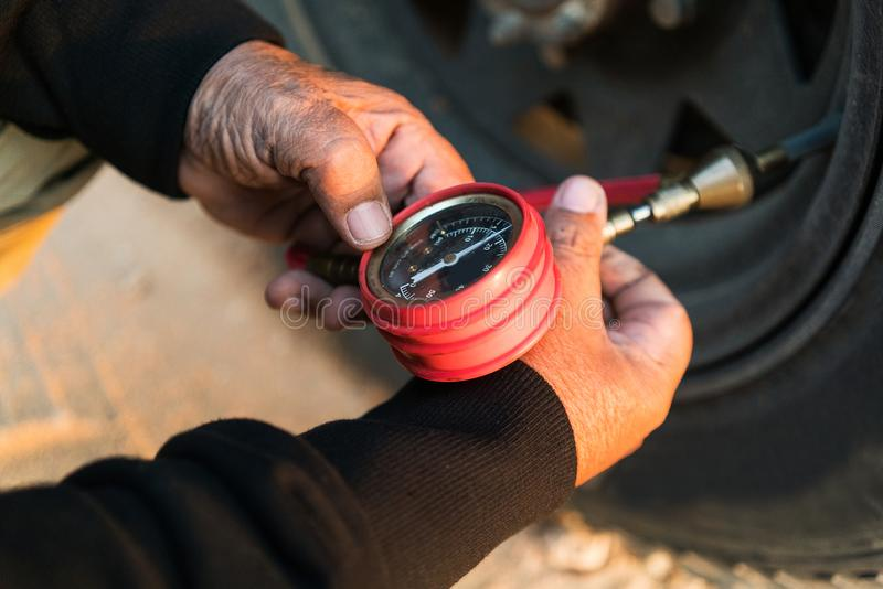 Pressão dos pneus de medição do homem com medidor Jipe 4x4 foto de stock royalty free
