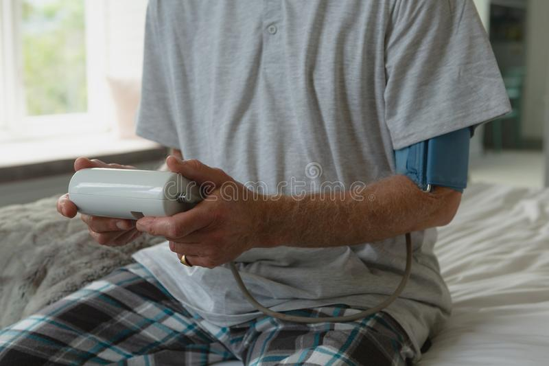 Pressão sanguínea de medição ativa de homem superior com o sphygmomanometer no quarto em casa imagens de stock royalty free