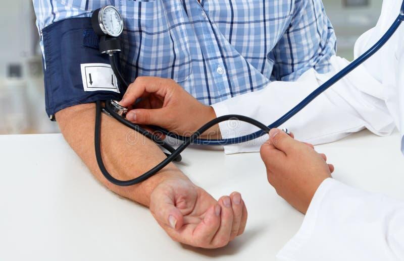 Pressão sanguínea de medição do doutor com sphygmomanometer foto de stock royalty free