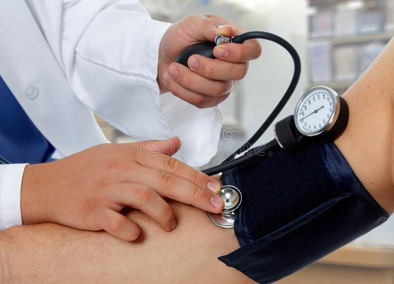Pressão sanguínea de medição do doutor com sphygmomanometer fotografia de stock