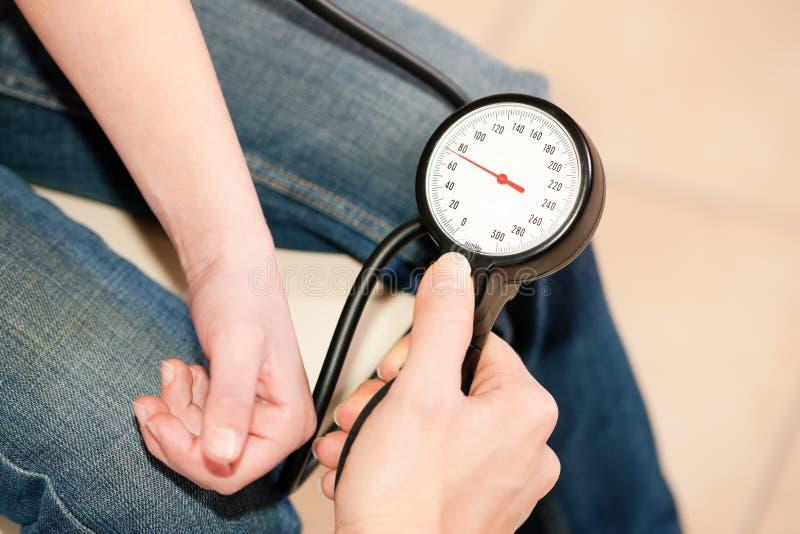 Pressão sanguínea de medição do doutor da criança imagem de stock