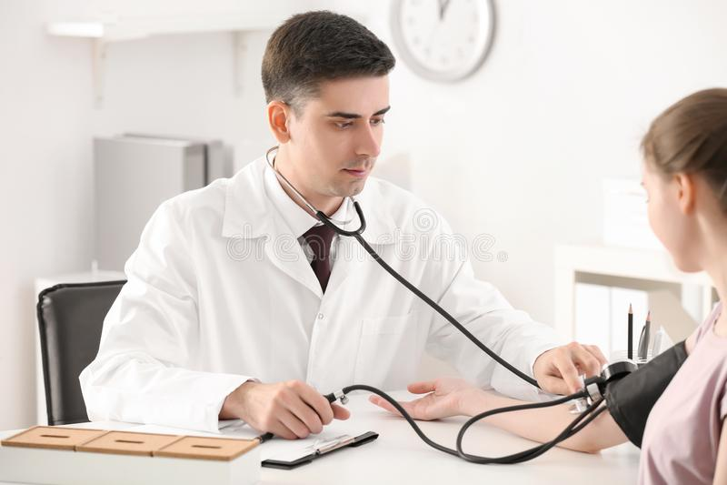Pressão sanguínea de medição do doutor masculino da jovem mulher no hospital imagens de stock
