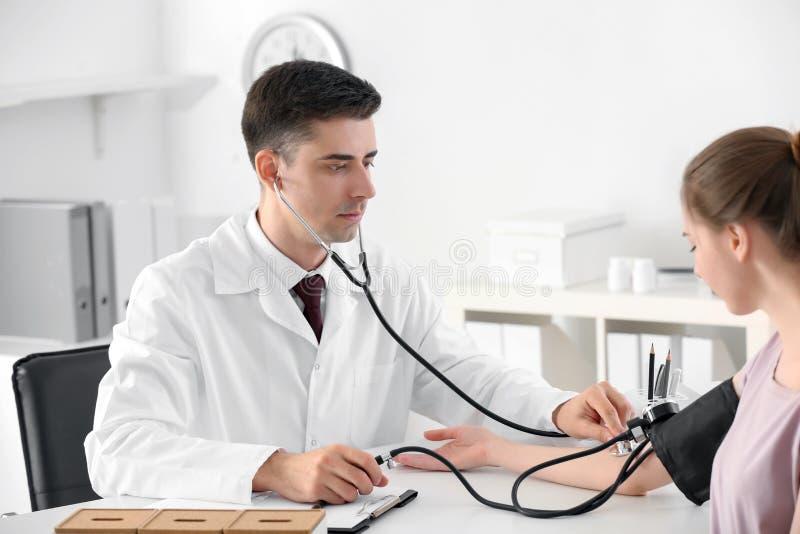 Pressão sanguínea de medição do doutor masculino da jovem mulher no hospital imagem de stock