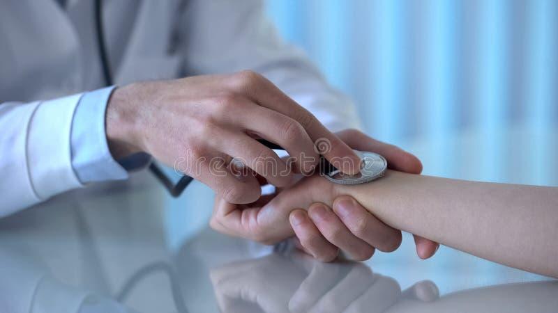 Pressão sanguínea de medição do doutor masculino profissional do paciente fêmea na clínica fotografia de stock