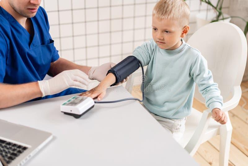 Pressão sanguínea de medição do doutor de um rapaz pequeno Diagnóstico, cuidados médicos, serviço médico Doutor Pediatra Concept foto de stock