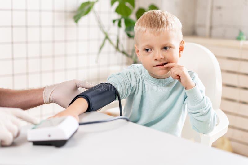 Pressão sanguínea de medição do doutor de um rapaz pequeno Diagnóstico, cuidados médicos, serviço médico Doutor Pediatra Concept imagem de stock royalty free