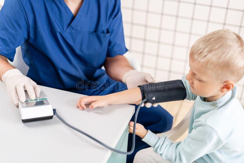 Pressão sanguínea de medição do doutor de um rapaz pequeno Diagnóstico, cuidados médicos, serviço médico Doutor Pediatra Concept fotografia de stock