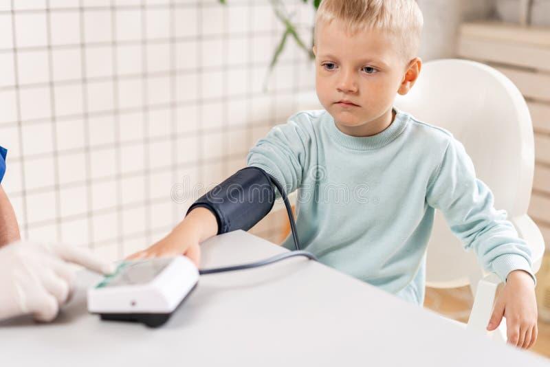 Pressão sanguínea de medição do doutor de um rapaz pequeno Diagnóstico, cuidados médicos, serviço médico Doutor Pediatra Concept imagem de stock