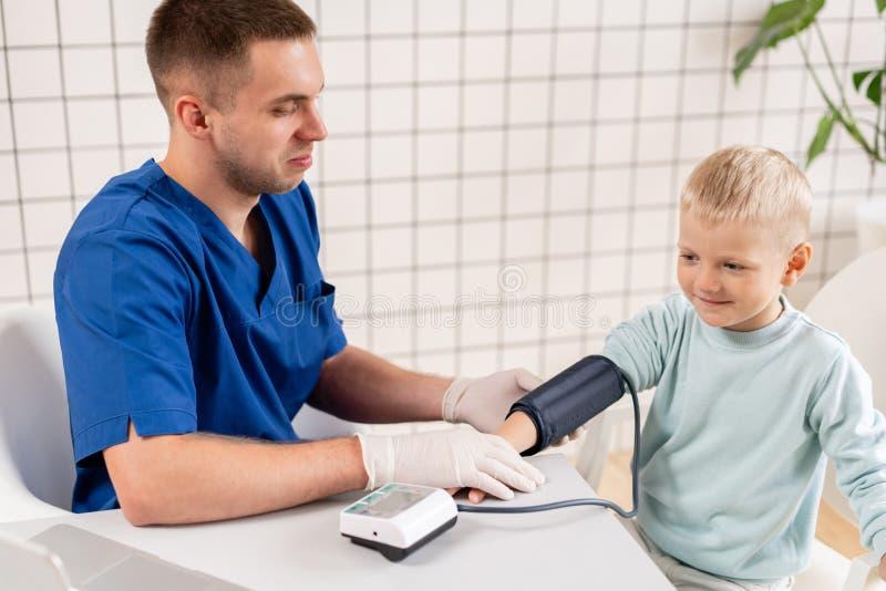 Pressão sanguínea de medição do doutor de um rapaz pequeno Diagnóstico, cuidados médicos, serviço médico Doutor Pediatra Concept fotografia de stock royalty free
