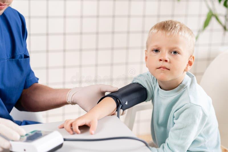Pressão sanguínea de medição do doutor de um rapaz pequeno Diagnóstico, cuidados médicos, serviço médico Doutor Pediatra Concept foto de stock royalty free