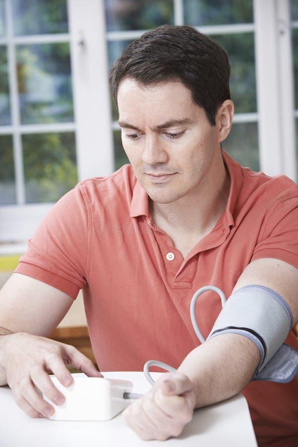 Pressão sanguínea de medição do homem em casa fotografia de stock