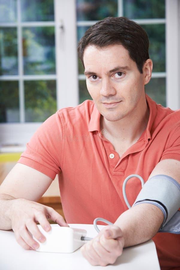 Pressão sanguínea de medição do homem em casa imagens de stock royalty free