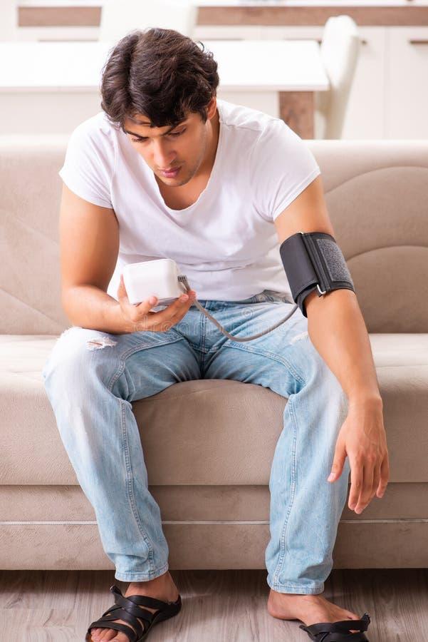 A pressão sanguínea de medição de homem novo em casa imagens de stock
