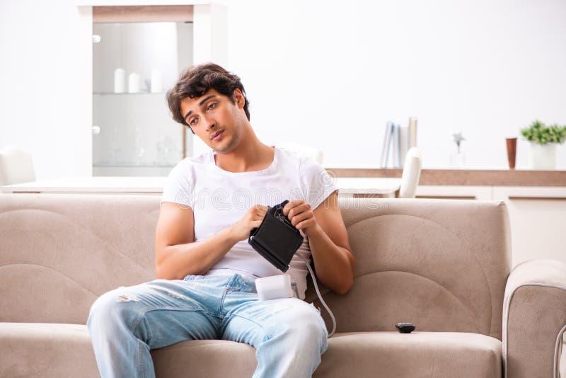 A pressão sanguínea de medição de homem novo em casa imagem de stock royalty free