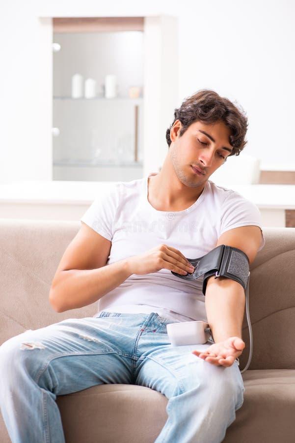 A pressão sanguínea de medição de homem novo em casa foto de stock royalty free