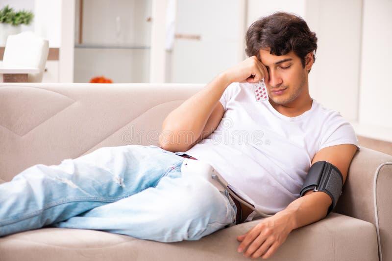 A pressão sanguínea de medição de homem novo em casa foto de stock
