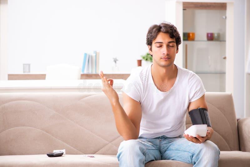 A pressão sanguínea de medição de homem novo em casa fotos de stock